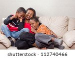 A loving mother sharing happy moments with her two sons - stock photo