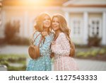 Small photo of Positive and adorable girls smiling and posing in rose and blue flowery dresses. Young beautiful ladies looking somewhere and holding stylish straw bags in their hands.