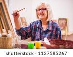elderly woman is painting in... | Shutterstock . vector #1127585267