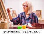 elderly woman is painting in... | Shutterstock . vector #1127585273