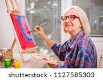 elderly woman is painting in... | Shutterstock . vector #1127585303