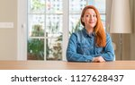 redhead woman at home smiling... | Shutterstock . vector #1127628437