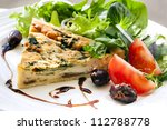 Spinach quiche with a healthy salad and balsamic glaze. - stock photo