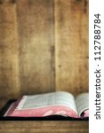 Old Bible, open on a wooden bookshelf.  With grunge effects. - stock photo