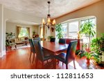 Dining and living room with plants and hardwood floor. - stock photo