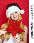beautiful blonde girl wearing a christmas hat is smiling - stock photo