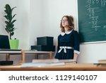sad schoolgirl standing in... | Shutterstock . vector #1129140107