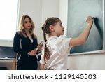 schoolgirl first grader writing ... | Shutterstock . vector #1129140503