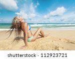 Young woman sitting on a sand of the tropical beach - stock photo