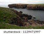 brown cliffs of a rocky coast... | Shutterstock . vector #1129471997