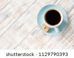 blue cup of black coffee on... | Shutterstock . vector #1129790393