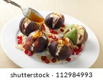 Fresh figs stuffed with mizithra sheep's cheese and toasted almond slivers, topped with honey and garnished with pomegranate seeds. - stock photo