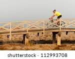 Strong middleaged man riding a bicycle over a wooden bridge at the seaside with the fresh air - stock photo