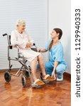nursing lady helps elderly... | Shutterstock . vector #1129940333