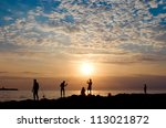 People fish. The sea, evening, the beautiful sky. - stock photo