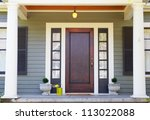 Brown stained Front Door on a home with bordering window and a pillared porch - stock photo