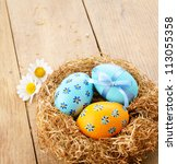 Nest with Easter eggs on the wooden table with copy-space - stock photo