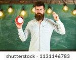teacher in eyeglasses holds... | Shutterstock . vector #1131146783