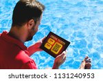 man holding a tablet with... | Shutterstock . vector #1131240953
