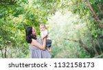 mother carries  child in summer ... | Shutterstock . vector #1132158173