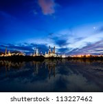 Oil refinery plant at twilight dark blue sky near river. - stock photo