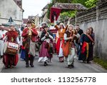 NOGENT LE ROTROU,FRANCE,MAY 19: Parade of medieval characters with old style band marching near the Saint Jean Castle during a historical reenactment festival on May 19,2012 in Nogent le Rotrou,France - stock photo
