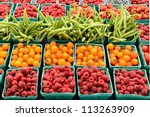 A vendor sales fresh organic berries at a local farmers market in Oregon - stock photo