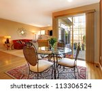 Elegant dining table near large door and living room. - stock photo