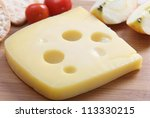 A wedge of Jarlsberg Danish cheese with crackers and cherry tomatoes on a cheeseboard - stock photo