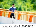 handsome man running on bridge. | Shutterstock . vector #1133455493