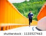 handsome man running on bridge. | Shutterstock . vector #1133527463