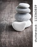 close up of four zen rocks on old wooden plank - stock photo