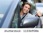 Young man doing thumps-up in car - stock photo