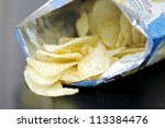 Opened pack of delicious spicy potato chips over black  table - stock photo