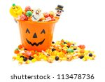 Jack-o-lantern candy pail with a pile of colorful Halloween candy - stock photo