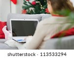 Woman using laptop near Christmas tree. Rear view - stock photo