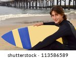 Surfer at an Orange County CA Beach/Male Teenage Surfer/Young teenager preparing for a morning surfing - stock photo