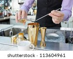 Bartender is adding ingredient in shaker at bar counter - stock photo