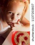 little girl eating appetizingly ... | Shutterstock . vector #1137203837