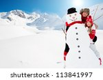 Winter fun, snowman and happy family - stock photo