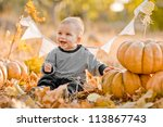 Happy Child With Pumpkins On...