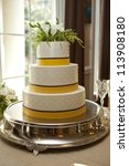 three tiered wedding cake in white, brown, and yellow. - stock photo