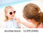 Mother applying sunblock cream on her daughters nose - stock photo