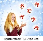 beautiful blonde woman holding a christmas gift is smiling - stock photo