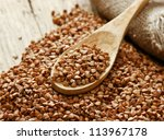 buckwheat groats and wooden spoon - stock photo