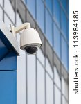 Surveillance camera on a background of blue glass wall - stock photo