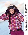 Smiling young woman wearing skiing suit posing outdoors in winter - stock photo
