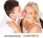 Young happy couple in love. Man kissing his girlfriend on white background - stock photo