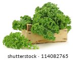 freshly harvested  kale cabbage in a wooden crate on a white background - stock photo