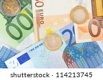Euro bills and some coins in front of a white studio background - stock photo